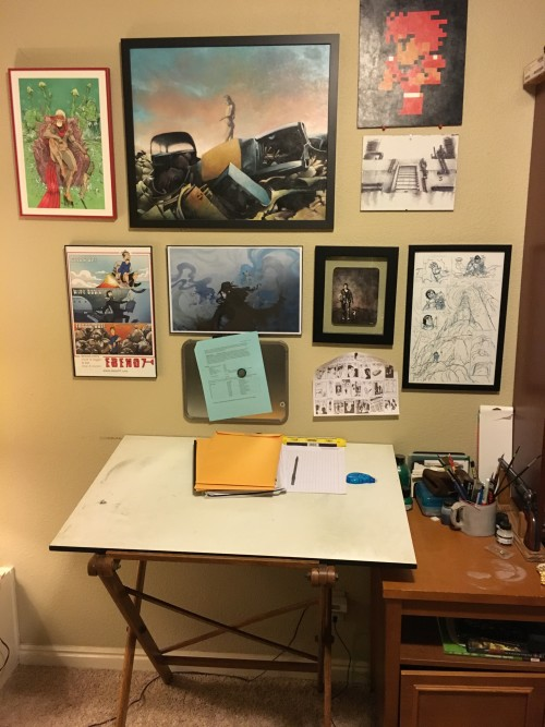 Art table (with some student portfolios I need to grade). Artwork by Giannis Milonogiannis, Josh Tobey, Melissa Pagluica, and Simon Roy are there to inspire me.